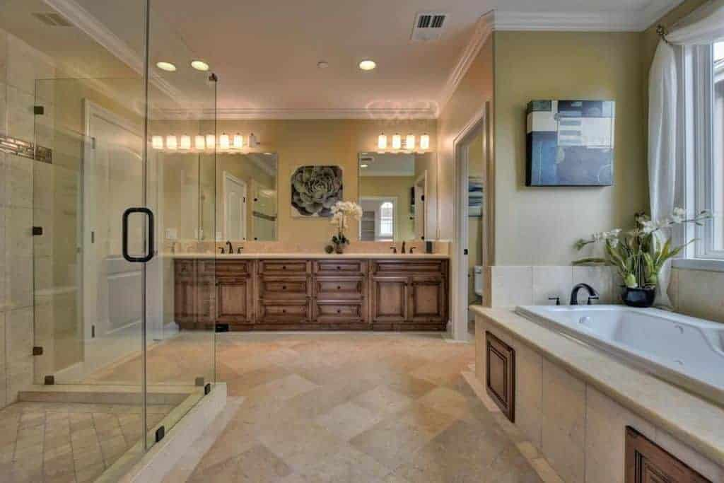 Large primary bathroom featuring a sink counter with two sinks lighted by wall lights along with a large walk-in shower room, a drop-in tub and a toilet room.