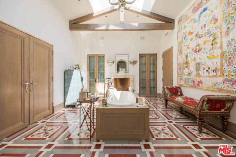 Large primary bathroom with stunning decorated flooring and a large wall decor. The room has a fireplace and a drop-in tub under the room's skylight.