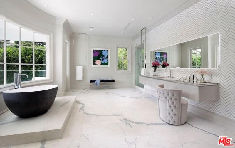 Spacious white primary bathroom featuring marble tiles flooring and a stylish wall. It has a floating vanity with space for a sink and a powder area. The room offers a corner walk-in shower room and a freestanding tub on a marble platform.