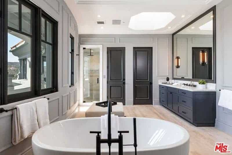 Primary bathroom featuring classy walls and a bright ceiling. The room offers a corner walk-in shower room, a sink counter and a large freestanding tub.