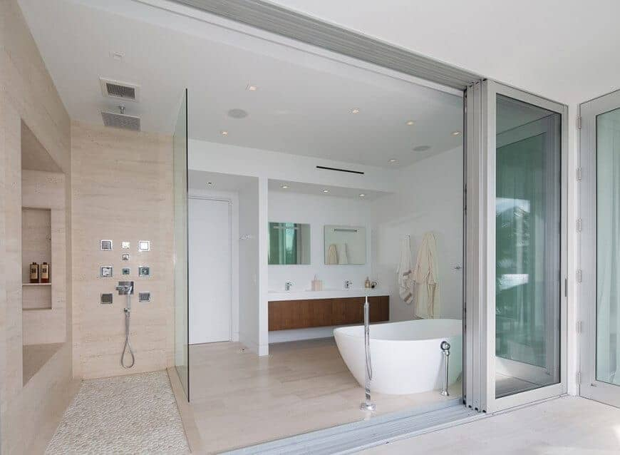 Primary bathroom featuring a walk-in shower area and a floating vanity with two sinks along with a freestanding tub.