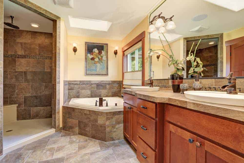 Primary bathroom featuring a walk-in shower room and a drop-in corner tub. The sink counter has two sinks and is lighted by wall lights.