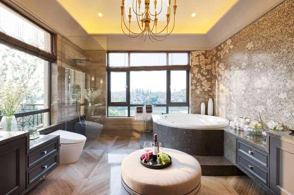 Large primary bathroom with gorgeous decorated walls and a stunning tray ceiling. The room features a drop-in corner tub and an open shower.