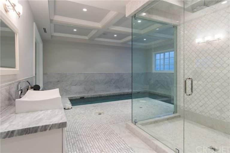 Primary bathroom boasting an indoor swimming pool. It has a coffered ceiling with recessed lights. There's a vessel sink and a large walk-in shower.