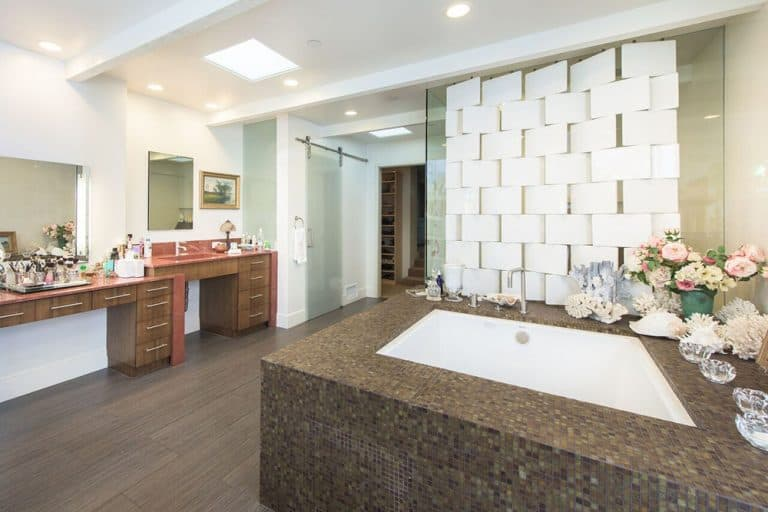 Large primary bathroom featuring a sink counter, a powder desk, a large square drop-in tub and a walk-in shower area. The room is connected to the home's walk-in closet too.