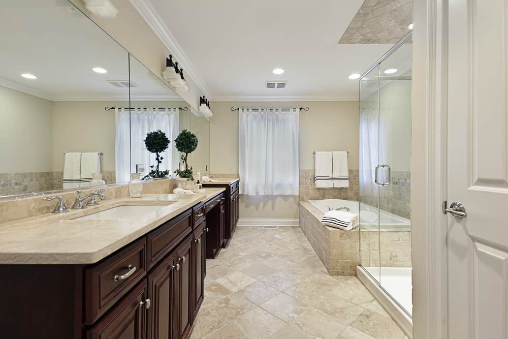 Large primary bathroom featuring a drop-in tub, a walk-in shower and a pair of sink counters along with a powder desk.