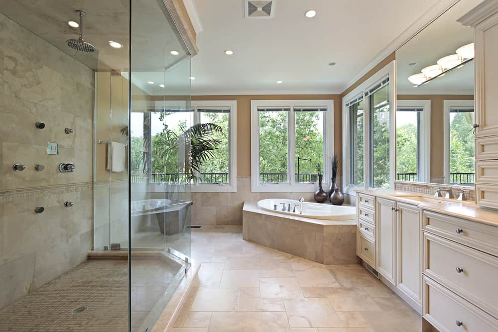 This primary bathroom features beige tiles flooring. The room offers a drop-in corner tub, a large walk-in shower room and a sink counter.