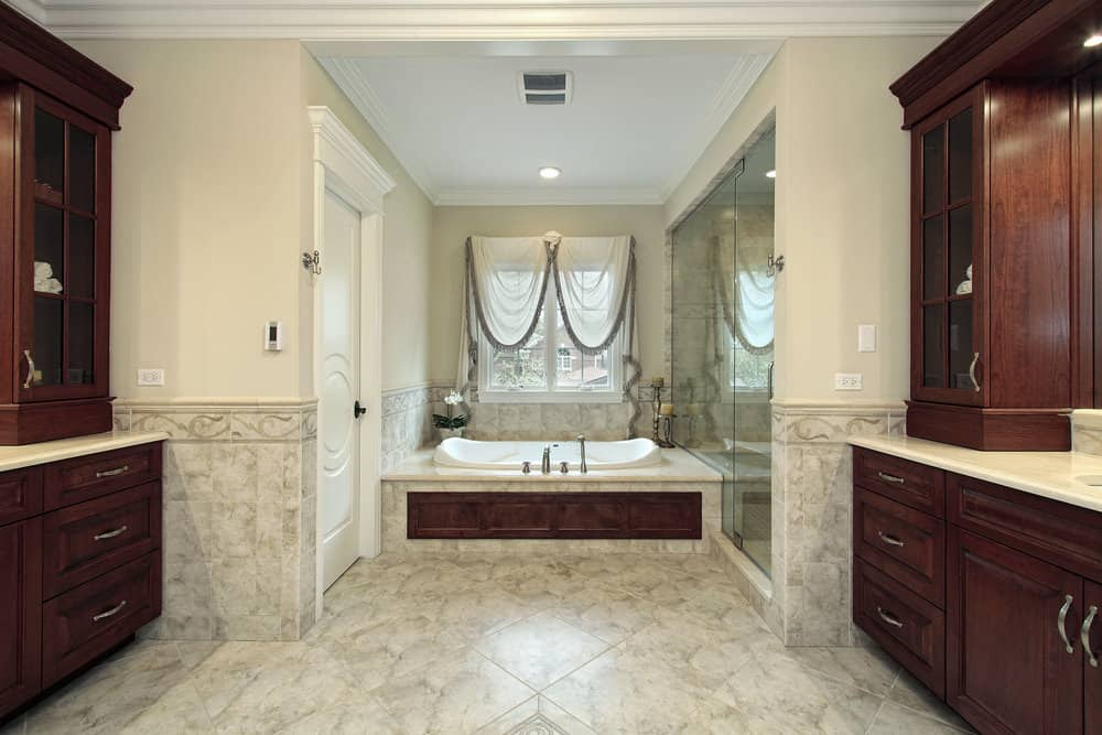 Large primary bathroom with two sink counters, a drop-in soaking tub and a large walk-in shower room. The bathroom also features stylish tiles flooring.