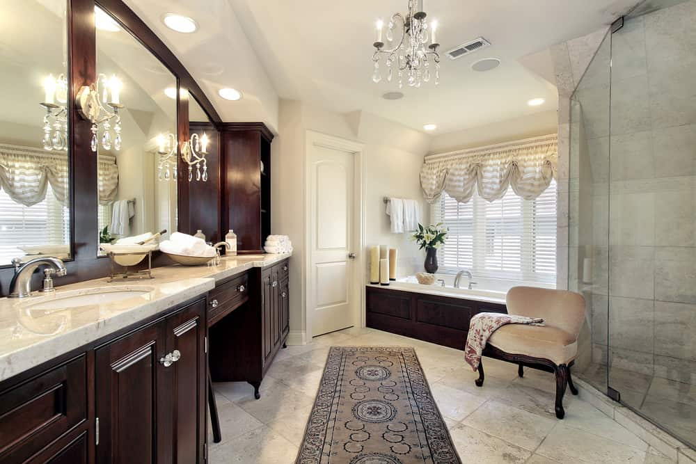 Bright primary bathroom featuring a walk-in corner shower room and two sink counters with a powder desk in between. There's a drop-in tub as well. The room is lighted by gorgeous chandelier.