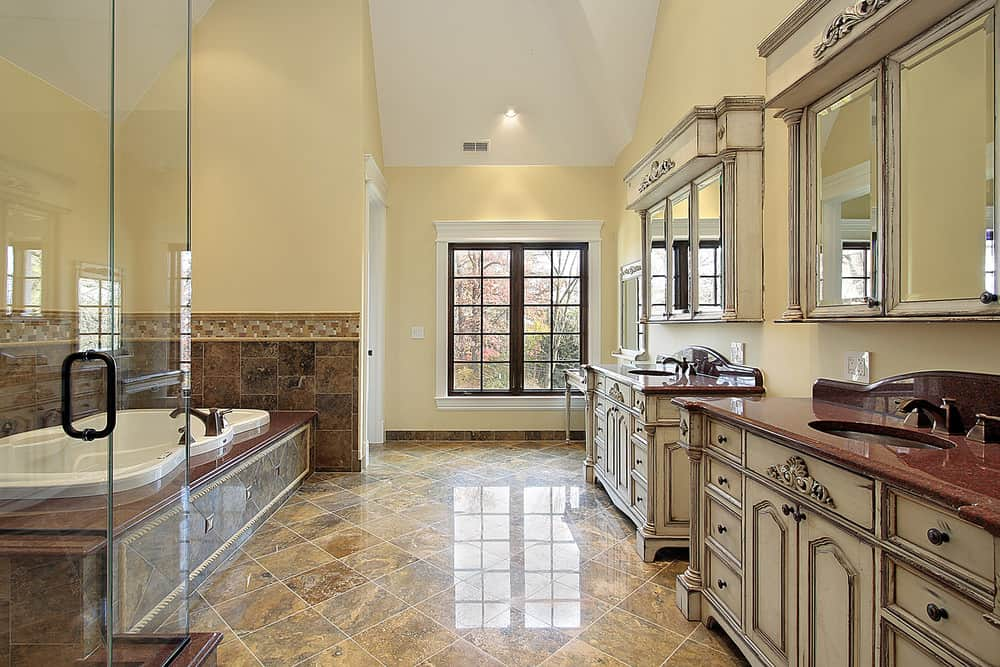 Spacious primary bathroom featuring brown tiles flooring and a tall ceiling. There are two sink counters that look classy. There's a deep soaking tub and a walk-in shower too.