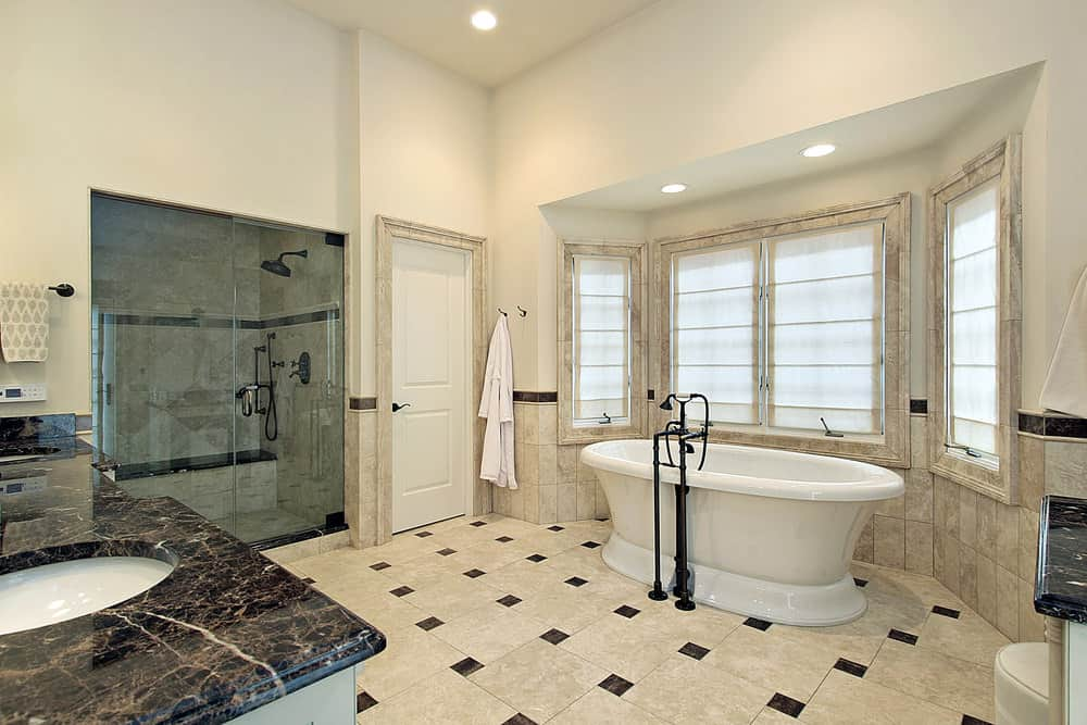 Primary bathroom with stylish tiles flooring and a tall ceiling. There's a black marble sink counter, a freestanding soaking tub and a walk-in shower room.