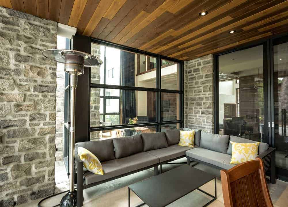 A living room featuring stone walls and wooden ceiling. There are glass windows and doors as well together with a cozy gray couch.