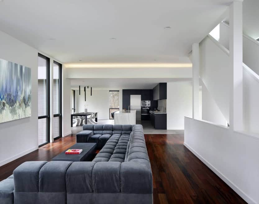This living area offers a massive gray sofa set along with a stylish gray center table set on the home's hardwood flooring.