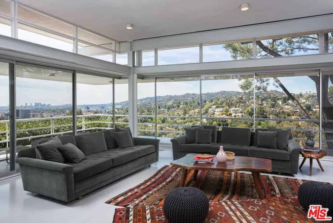 A large living space featuring glass walls and windows along with gray couches and a rug.