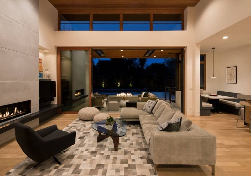 A large modern living space featuring a stylish area rug along with a gray sofa set and a glass top center table. There's a fireplace as well.