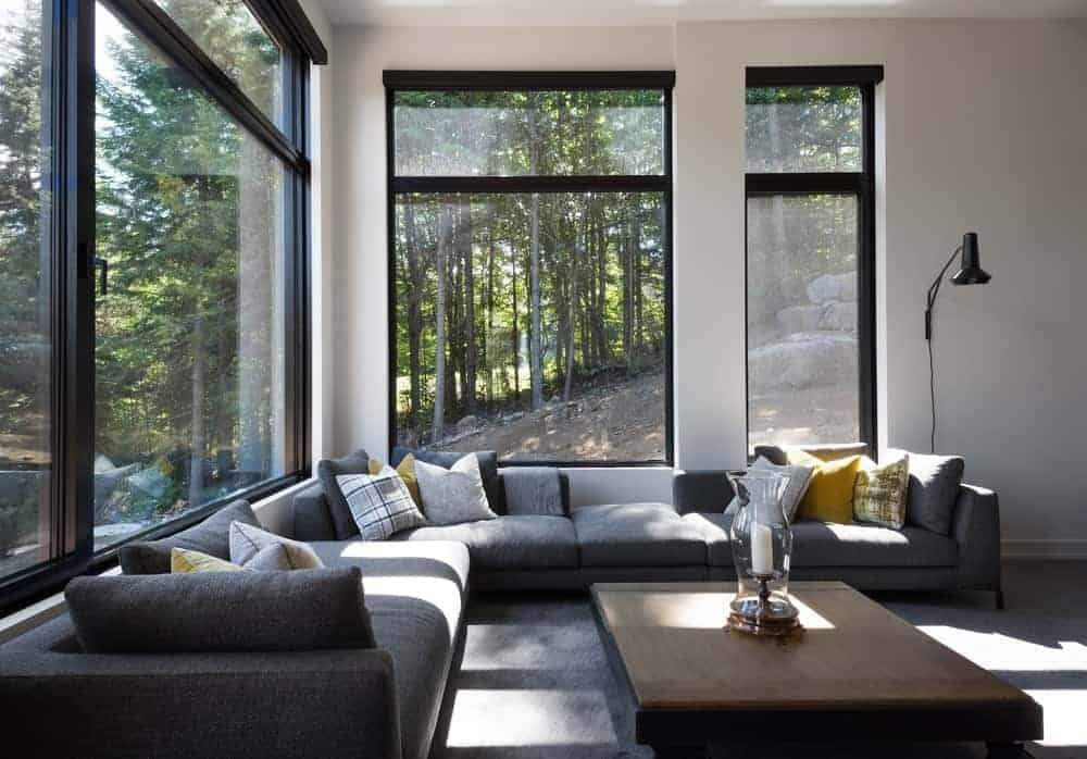 This living room offers an L-shaped gray sofa set with large glass windows with black frame.