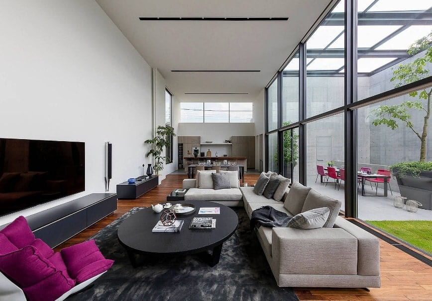 A nice living space that offers a large widescreen TV on the wall along with an L-shaped gray couch paired with a black round center table.