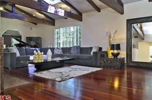 Spacious living space featuring hardwood flooring and a ceiling with exposed beams. There's a large gray sofa set with a stylish center table as well.