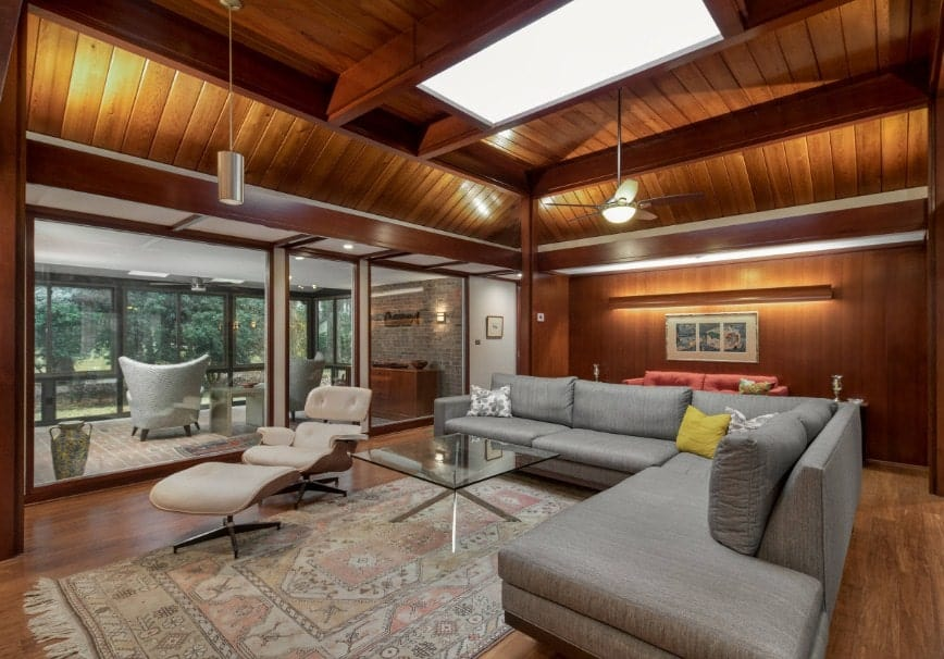 A Mediterranean living room with wooden ceiling with exposed beams boasting a skylight. The room offers an L-shaped sofa paired with a glass top center table.