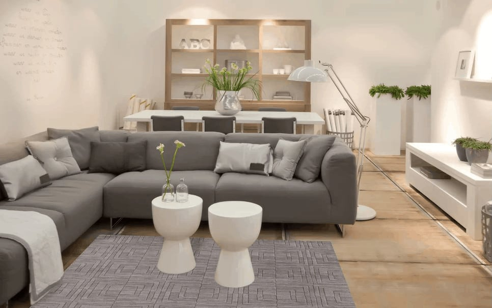 This living space features brown flooring and white walls. It offers an L-shaped gray sofa and a gray stylish rug with two white center tables on it.