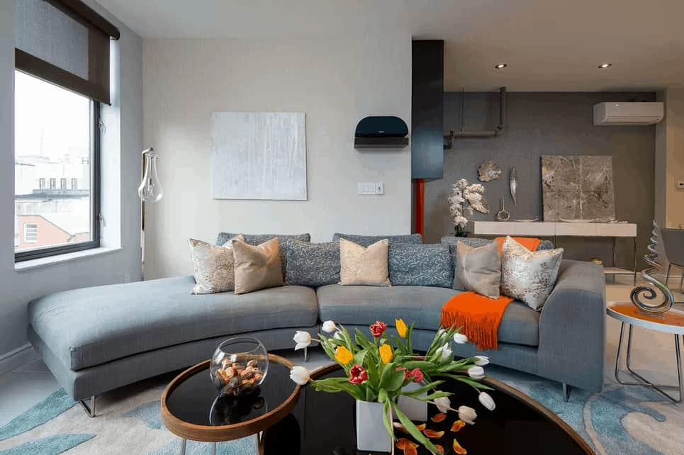 This living room features a curved modish gray couch set on a beautiful rug. There's a stylish center table as well.