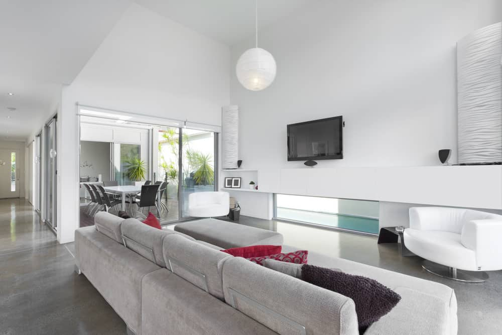 White living space featuring gray flooring and light gray couch along with a TV on the wall. The area also has a tall ceiling with a pendant light.
