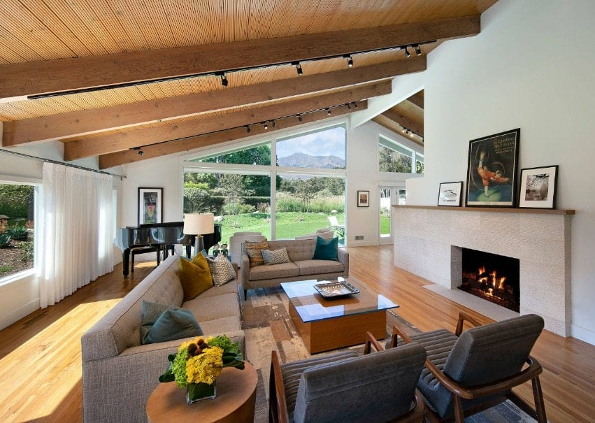 A Mediterranean living room featuring hardwood flooring and a shed ceiling with beams lighted by track lights. The room offers a set of cozy seats and a fireplace.