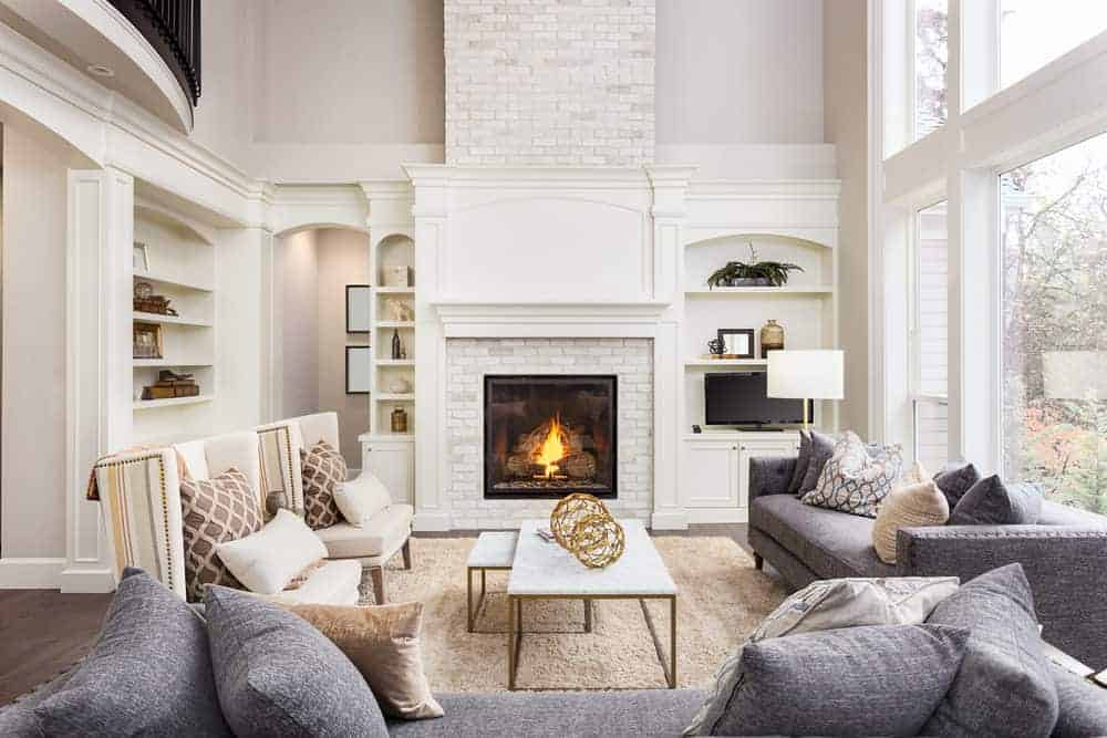 White living room featuring a set of gray couches along with a fireplace with multiple built-in shelves on its side.