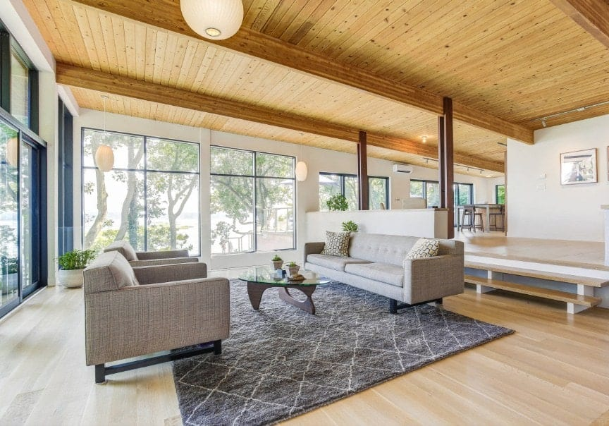 Large living room featuring a tall wooden ceiling with exposed beams. The room also offers gray couches and a glass top center table set on a large gray area rug.