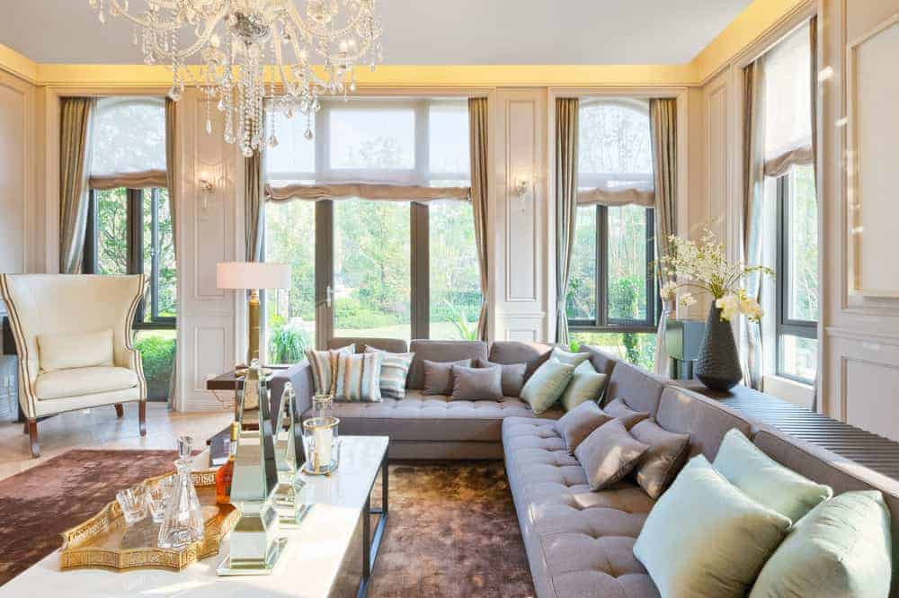 This living room boasts elegant windows and a glamorous chandelier lighting up the space. There's a large L-shaped sofa set on a classy rug.