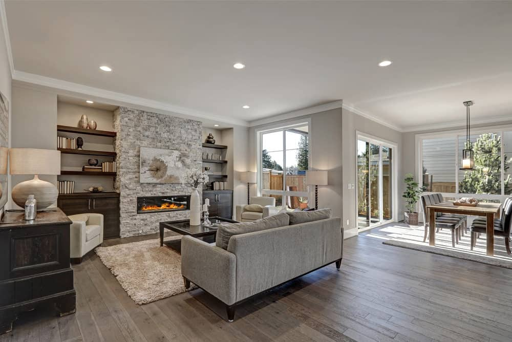 A spacious living space featuring hardwood flooring and a stone fireplace along with built-in shelves and cabinet. There's a gray couch as well.