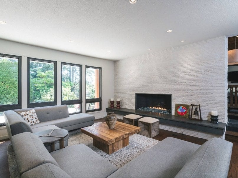 This living room offers gray couches, a rustic center table and a fireplace along with glass windows.