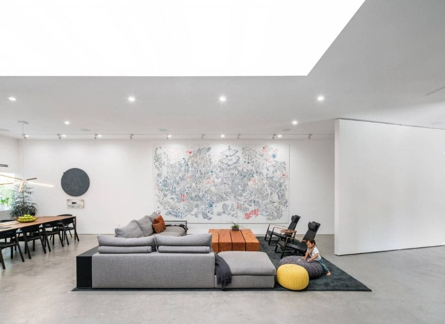 A spacious living space featuring a large gray sofa set on a black area rug along with a stylish center table.