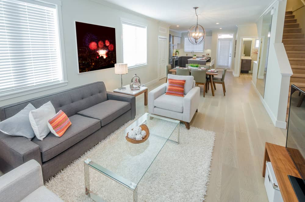 Bright living space with a gray couch and white seats on the side along with a glass top center table.