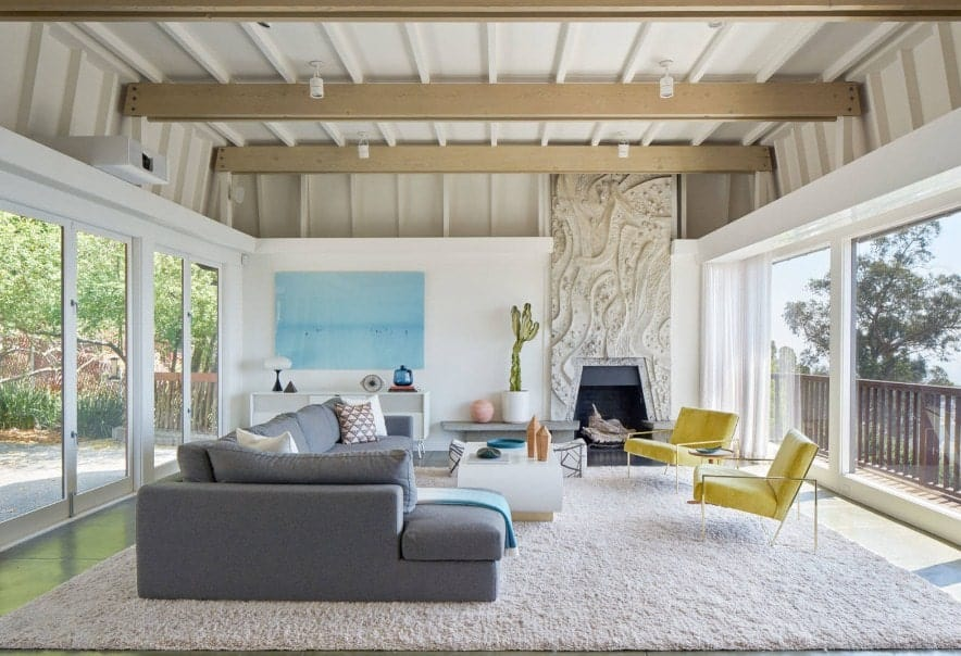 Large living room with a tall ceiling with exposed beams lighted by track lights. There's also a gray sofa set and a large area rug along with a fireplace.