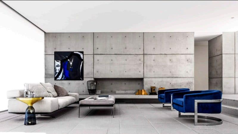 A bright living room featuring a gray wall and flooring. It also has a set of blue seats and a light gray couch.
