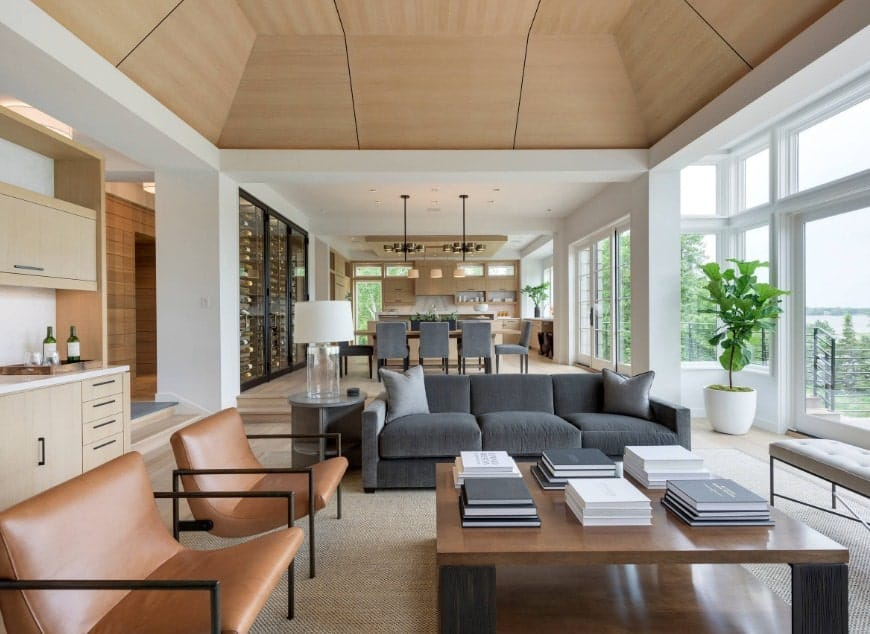 This living room offers a gray sofa set along with brown seats and a large center table, all under the stunning tall ceiling.