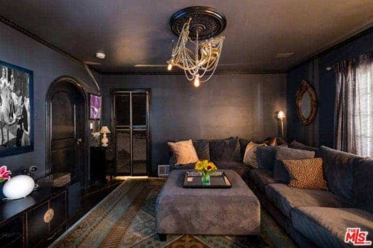 This living room features a gloomy vibe with its dark walls and ceiling. It also features a large L-shaped gray sofa with a large gray ottoman.