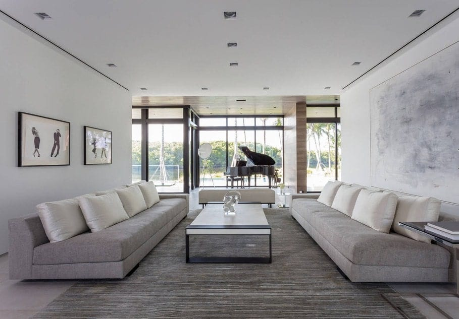 This living room offers two large gray couches along with attractive wall decors and a large center table.
