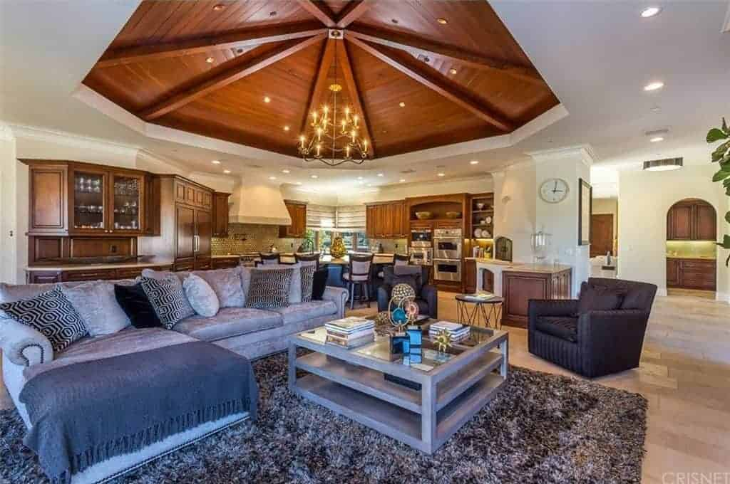 Large living space boasting a stunning custom-designed ceiling lighted by warm lighting along with a cozy sofa set with a glass top center table.