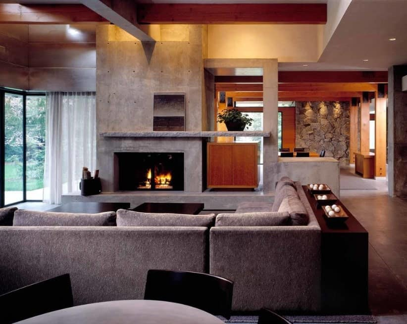 A modern living space featuring a cozy gray sofa set along with two center tables and a fireplace.