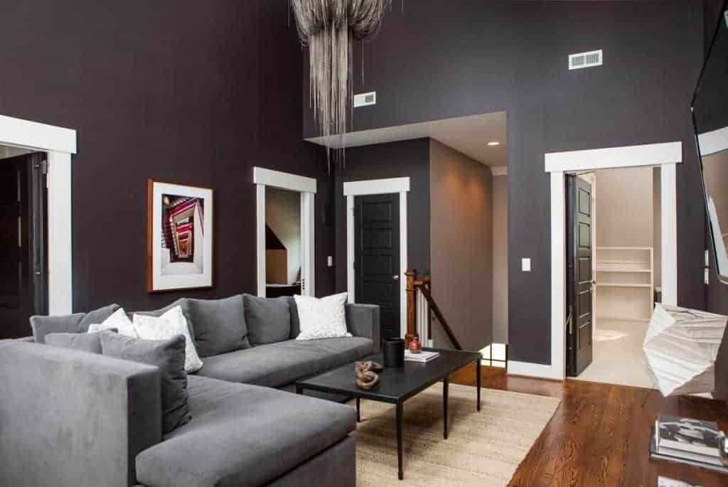 A living room surrounded by black walls with a white accent. It offers a gray sofa set with a black center table.