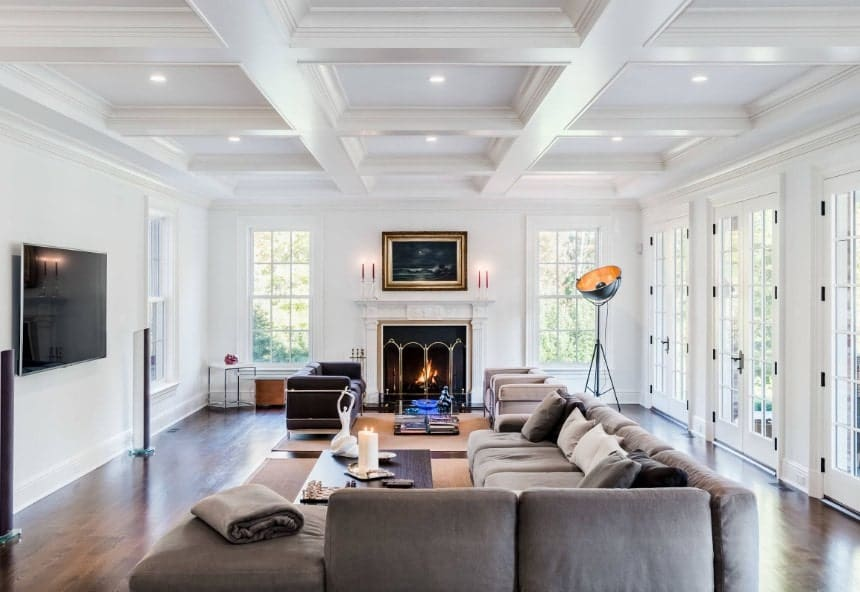 Large white living space featuring a large gray sofa set along with a fireplace and a TV on the wall. The white coffered ceiling adds class to the area.
