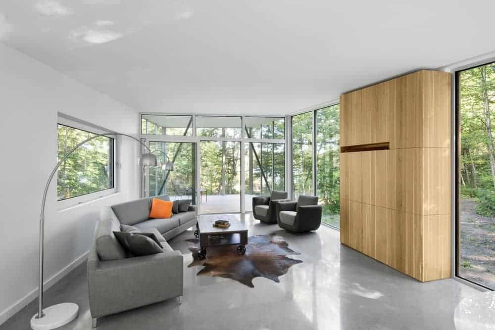 This spacious living room features glass windows and walls. The area also offers gray couches and a stylish rug.
