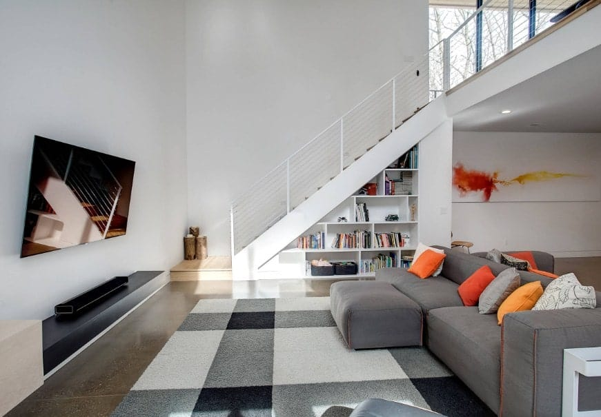 This living room offers a comfy gray couch with an ottoman set on the stylish area rug. There's a large widescreen TV in front.