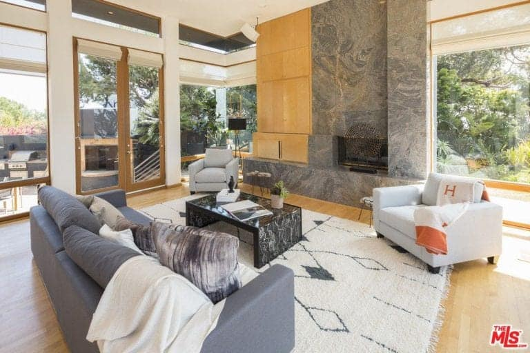A spacious living room featuring gray couches and a stylish center table set on the rug.