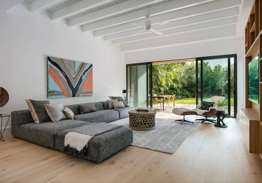 A white living room featuring an L-shaped gray sofa set along with an artistic wall decor. The room has a ceiling with beams along with hardwood flooring.