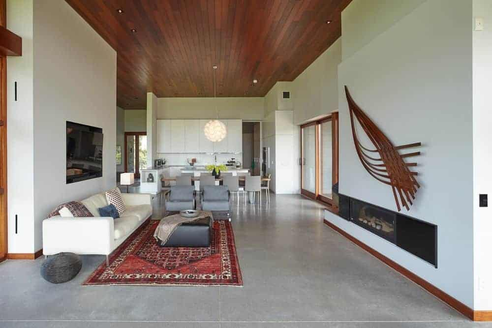 A great room featuring a white couch, a red rug, a gas fireplace and a tall wooden ceiling.