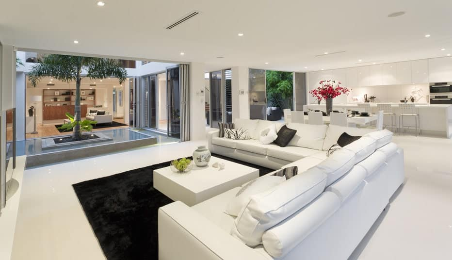 Large white great room featuring a nice white living space with an L-shaped sofa, a white dining table set and a white kitchen with a large center island with a breakfast bar.