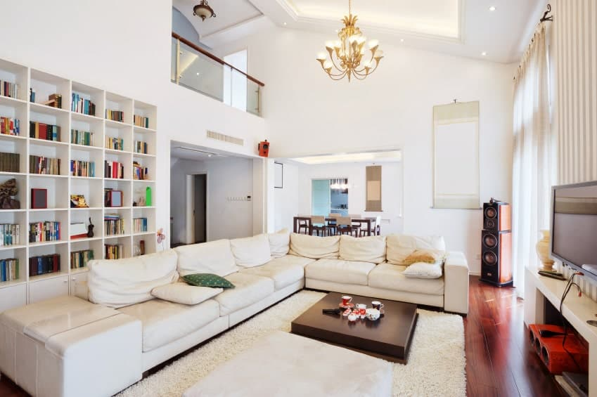 Large living space with a large L-shaped couch along with large white bookshelf lighted by a beautiful chandelier.